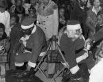 Charles B. Washington and another man dressed as Santa Claus distributing presents to children