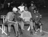 Charles B. Washington sitting on bench with young people